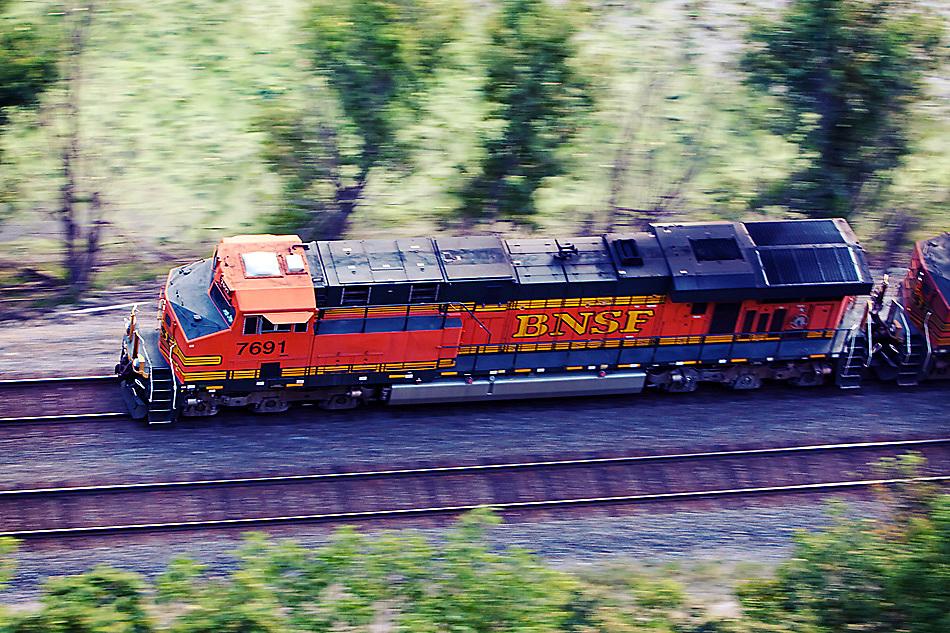 A new BNSF General Electric locomotive speeds along the Mississippi River bluffs near Savanna, IL.