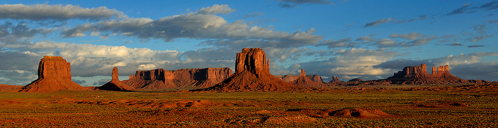 "Monument Valley (Navajo: Tsé Bii' Ndzisgaii, meaning valley of the rocks) is a region of the Colorado Plateau characterized by a cluster of vast sandstone buttes, the largest reaching 1,000 ft (300 m) above the valley floor. It is located on the Arizona-Utah state line near the Four Corners area. The valley lies within the range of the Navajo Nation Reservation.  The area is part of the Colorado Plateau. The elevation of the valley floor ranges from 5,000 to 6,000 feet (1,500 to 1,800 m) above sea level. The floor is largely siltstone of the Cutler Group, or sand derived from it, deposited by the meandering rivers that carved the valley. The valley's vivid red color comes from iron oxide exposed in the weathered siltstone. The darker, blue-gray rocks in the valley get their color from manganese oxide.  The buttes are clearly stratified, with three principal layers. The lowest layer is the Organ Rock Shale, the middle is de Chelly Sandstone, and the top layer is the Moenkopi Formation capped by Shinarump Conglomerate. The valley includes large stone structures including the famed ""Eye of the Sun""."