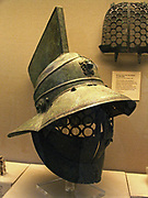 This bronze helmet is said to have been found in the gladiators' barracks at Pompeii. It has a grille of linked circles to protect the face and a broad brim to protect the back and sides of the head. At the front of the helmet is a medallion of Hercules, symbolizing strength and victory. Although gladiators were sometimes slaves or criminals, many were professionals who trained to be a specific type of gladiator, such as the retiarius armed with net and trident, or the samnite, a more heavily armed gladiator who wore this type of helmet.