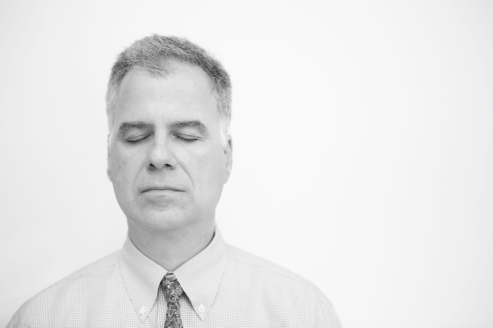 Black and white portrait photograph of middle age man meditating quietly