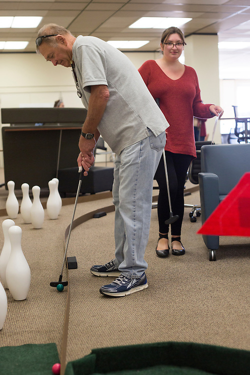 Doug Steinsieck, left, from Florida, plays mini golf in Alden Library with his daughter Abby, a freshman, during Dad's Weekend on November 5, 2016.