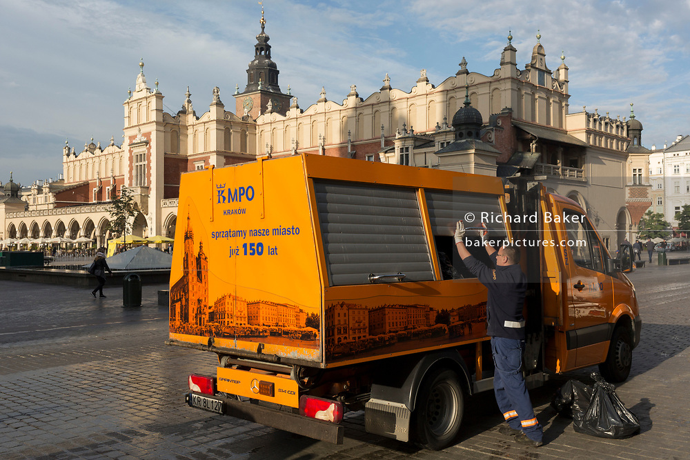 A city authority worker oversees the emptying of trash into a Mercedes Sprinter waste collection vehicle opposite the renaissance Cloth Hall during morning rubbish duties on Rynek Glowny market square, on 23rd September 2019, in Krakow, Malopolska, Poland.