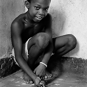 Jorge Suarez, age 10, plays a round of marbles in the passageway in front of his mother's apartment in the neighborhood of Jesus Maria, La Habana, Cuba, 1999. Photo by Jen Klewitz