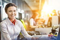 Portrait of young attractive passenger service agent working in airport with lens flare