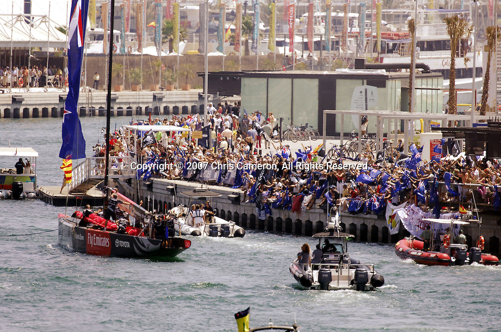 Emirates Team New Zealand NZL84 and NZL92 pass crowds of kiwi fans with flags as they tow out for race two of the 32nd America`s Cup in Valencia, Spain on Sunday 24 June 2007. Team New Zealand won the match by 28 seconds. Photo : Chris Cameron/PHOTOSPORT