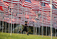 A boy runs through amongst 3,000 US flags are displayed at Pepperdine University to mark the 12th anniversary of the 9/11 terror attack, September 10, 2013 in Malibu, California. Photo by Ringo Chiu/PHOTOFORMULA.com)