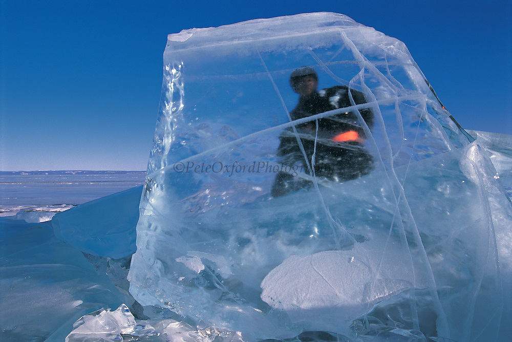 Darkhad man<br /> Ice chunks on lake shore<br /> Lake Hovskol<br /> Mongolia