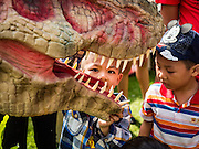 09 JANUARY 2016 - BANGKOK, THAILAND: Children look at robotic dinosaur during Children's Day festivities at Government House. National Children's Day falls on the second Saturday of the year. Thai government agencies sponsor child friendly events and the military usually opens army bases to children, who come to play on tanks and artillery pieces. This year Thai Prime Minister General Prayuth Chan-ocha, hosted several events at Government House, the Prime Minister's office.         PHOTO BY JACK KURTZ