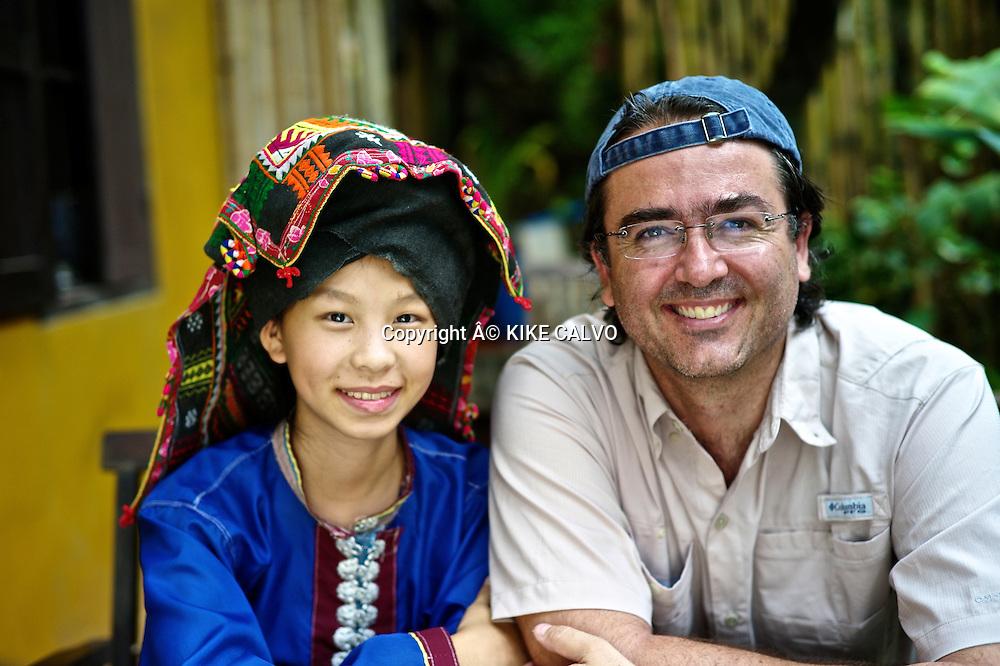 Photographer Kike Calvo with teen girl wearing Tai Dam traditional dress in Laos. Its used in Luang Prabang province.