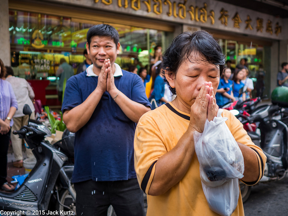 12 OCTOBER 2015 - BANGKOK, THAILAND: People pray as Buddhist monks pass them on Yaowarat Road the first day of the Vegetarian Festival in Bangkok's Chinatown. The Vegetarian Festival is celebrated throughout Thailand. It is the Thai version of the The Nine Emperor Gods Festival, a nine-day Taoist celebration beginning on the eve of 9th lunar month of the Chinese calendar. During a period of nine days, those who are participating in the festival dress all in white and abstain from eating meat, poultry, seafood, and dairy products. Vendors and proprietors of restaurants indicate that vegetarian food is for sale by putting a yellow flag out with Thai characters for meatless written on it in red.      PHOTO BY JACK KURTZ