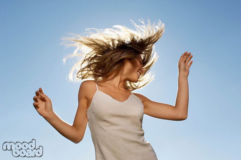 Young woman standing in front of sun tossing hair low angle view