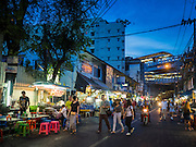12 JUNE 2015 - BANGKOK, THAILAND:     People walk past street food stalls on Sukhumvit Soi 38 in Bangkok, one of the most famous street food locations in the Thai capital. The food carts and small restaurants along the street have been popular with tourists and Thais alike for more than 40 years. The family that owns the land along the soi recently decided to sell to a condominium developer and not renew the restaurant owners' leases. More than 40 restaurants and food carts will have to close. The first wave of closings could start as soon June 21 and all of the restaurants are supposed to close over the next several months.  PHOTO BY JACK KURTZ