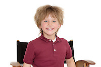 Portrait of a happy school boy sitting on director's chair over white background
