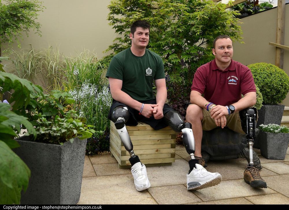 © Licensed to London News Pictures. 21/05/2012. Chelsea, UK. Royal Engineers Captain Dave Henson (L) and Sergeant Craig Gadd (R ) sit in The Courtyard Garden at the 2012 RHS Chelsea Flower Show the garden reflects the steps to recovery that wounded soldiers will make as they work within the new Therapy Garden that is currently being constructed at Headley Court. Press preview of The Chelsea Flower Show today 21 May 2012. The world's most famous flower show, which has been held in the grounds of the Royal Chelsea Hospital since 1913, will be open to the public from Tuesday. Visitors are expected to flock in their thousands to see displays of plants, flowers and furniture for ideas on how to decorate their gardens.. Photo credit : Stephen Simpson/LNP