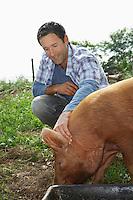 Man holding pig in sty