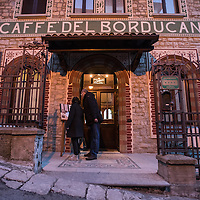A couple checks the menu of the Caffè del Borducan in Santa Maria del Monte near Varese, Italy