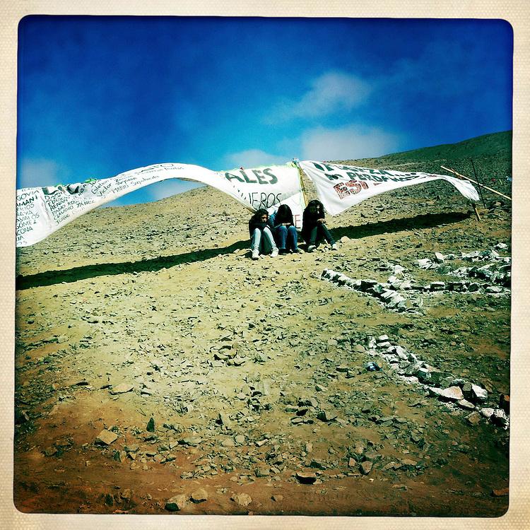 """Familiares de los mineros esperan en uno de los cerros cercanos al campoamento Esperanza. Plan B, es un ensayo fotografico basado en aquellas cosas que la mirada somera no permite ver, de los días de espera, angustia, soledad y fe que las familias de los 33 hombres atrapados en la mina San Jose dejaron en el paisaje arido del desierto de Atacama tras el esperado rescate. """"Plan B"""", tambien es un acto de fe personal, por intentar plasmar en un relato diferente, sin más pretensión que la mirada interna a los sentimientos que esa montaña atrapó implacable y para siempre, pero que bajo la mirada superficial de los medios no permite escudriñar por tratarse de pequeños fragmentos que apelan a emociones individuales y no a la masividad que persiguen los reportes de prensa. Este ensayo es una invitación abierta a descubrir los pequeños milagros que florecieron en la montaña y en el día a día de cada una de las familias que nunca dejaron de creer en la vida, aun así se enfrentaran a la inmensidad del desierto y a las minimas espectativas de vida que el lugar entregaba.""""Plan B"""", esta constituido por fotografías ejecutadas en su totalidad con un telefono iPhone 4 y la aplicacion Hipstamatic. ROBERTO CANDIA / REVISTA NUESTRA MIRADA"""