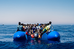 MEDITERRANEAN SEA, LIBYA - JUNE 15 :  Refugees wait to get on onboard the rescue vessel Golfo Azzurro by members of the Spanish NGO Proactiva Open Arms, after being rescued from a wooden boat sailing out of control in the Mediterranean Sea near Libya on Thursday, June 15, 2017. A Spanish aid organization Thursday rescued 420 migrants who were attempting the perilous crossing of the Mediterranean Sea to Europe in packed boats from Libya. Marcus Drinkwater / Anadolu Agency  | BRAA20170615_366 Mediterranean Sea Libye Libya