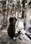happy smiling elderly couple on a sunny day posing with bicycle in the background Netherlands 1950s