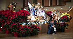 Visitors to the Cathedral of Our Lady of the Angels in downtown Los Angeles pose for a photo next to a Christmas display. The Roman Catholic cathedral was designed by Rafael Moneo in a postmodern style. The cathedral opened in 2002, replaced the Cathedral of Saint Viviana which was severely damaged in a 1994 earthquake.