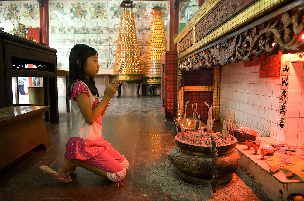Young Bruneian girl praying at the Chinese Temple