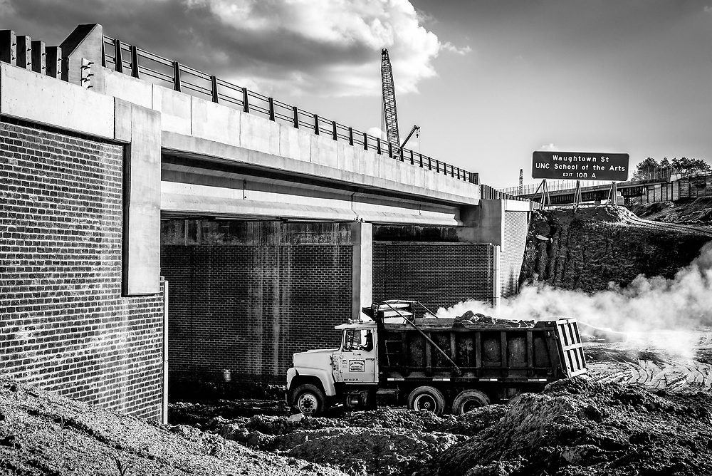 The hard lines and shapes of the bridge & truck contrast with the soft lines of the clouds, soil and smoke.