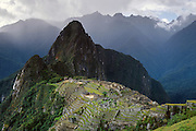 "A rain storm breaks over Machu Picchu, a magnificent Inca archeological site in the Cordillera Vilcabamba, Andes mountains, Peru, South America. Machu Picchu was built around 1450 AD as an estate for the Inca emperor Pachacuti (14381472). Spaniards passed in the river valley below but never discovered Machu Picchu during their conquest of the Incas 1532-1572. The outside world was unaware of the ""Lost City of the Incas"" until revealed by American historian Hiram Bingham in 1911. Machu Picchu perches at 2430 meters elevation (7970 feet) on a well defended ridge 450 meters (1480 ft) above a loop of the Urubamba/Vilcanota River ( Sacred Valley of the Incas). UNESCO honored the Historic Sanctuary of Machu Picchu on the World Heritage List in 1983."
