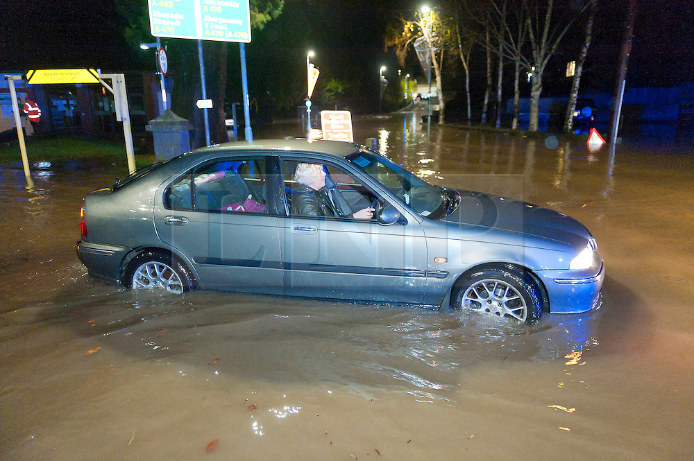 © Licensed to London News Pictures. 30/11/2015. Builth Wells, Powys, Wales, UK. Drivers return to their cars at The Groe Car park to find them surrounded by flood water. Parts of the Mid Wales market town Builth Wells became flooded late Monday afternoon when the river Wye burst it's banks near The Groe Car Park. Photo credit: Graham M. Lawrence/LNP