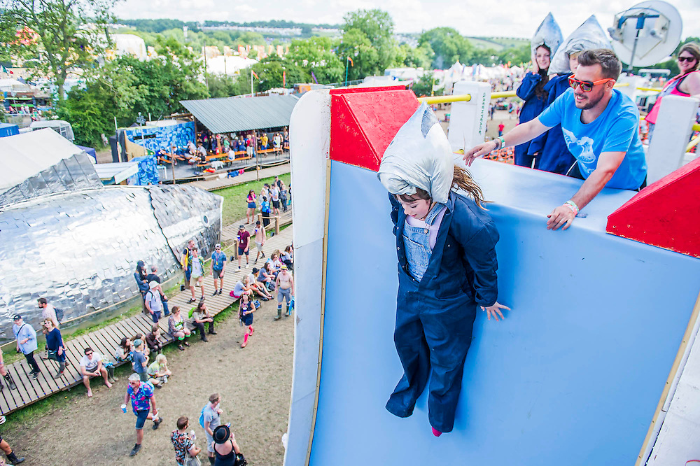 The Greenpeace area - a mock up of a factory fishing vessel (to highlight sustainability) includes a vertical drop slide for visitors of all ages to brave - they are dressed in overalls with 'tuna' heads. The 2015 Glastonbury Festival, Worthy Farm, Glastonbury.