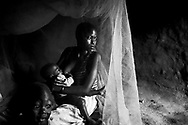 This young woman is breastfeeding under the mosquito net, to protect herself and her children from the deadly malaria virus. Mosquito nets are the most effective way to avoid malaria.
