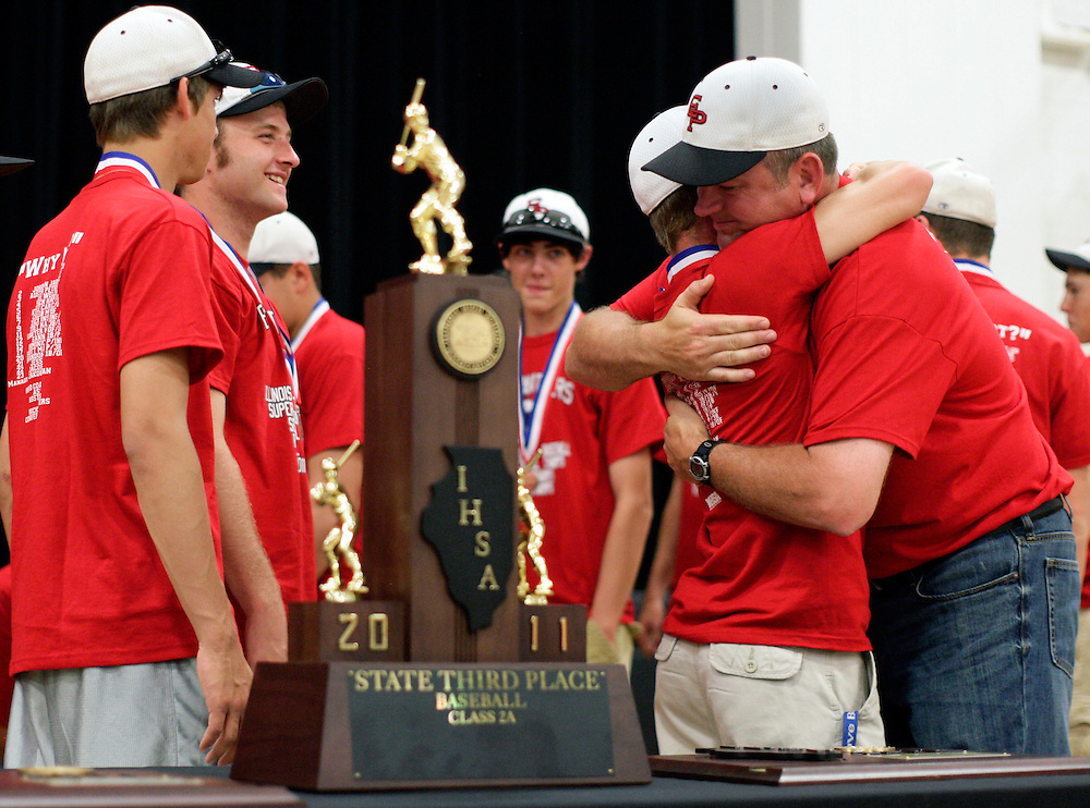 (20110605, Prophetstown, Illinois)..Erie-Prophetstown head coach Jason Orman, right, hugs players at an event on Sunday, June 5, 2011 at the Prophetstown High School gymnasium to celebrate the team's 3rd place finish in the Illinois State Class 2A baseball championships...Moline Dispatch, Brooks Canaday.