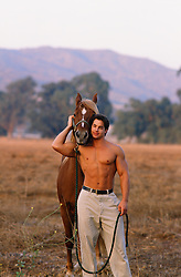 shirtless muscular man with a horse on a ranch