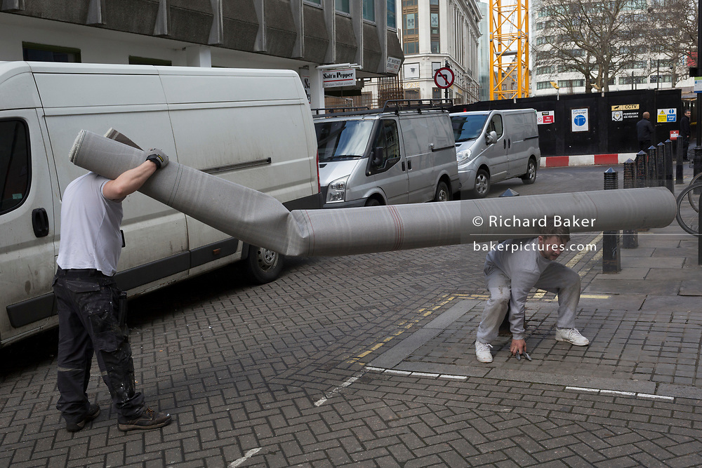 Deliverymen struggle carry a long roll of carpet into a nearby building off Leicester Square, on 5th March 2018, in London, England.
