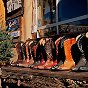 Western boots lined up on bench outside shop, Sante Fe, New Mexico