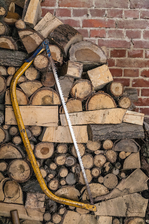 firewood stacked against brick wall with saw propped against