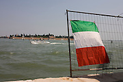 A speedboat passes the Italian flag on Venice's Canale delle Fondamenta Nuove in the Cannaregio district.