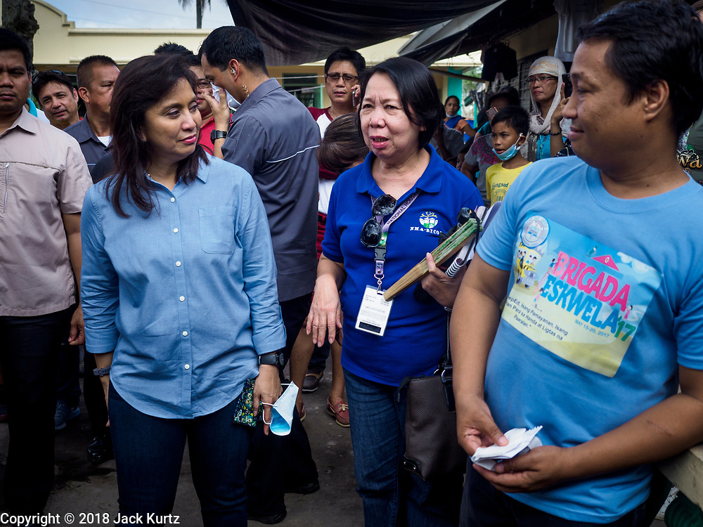 24 JANUARY 2018 - GUINOBATAN, ALBAY, PHILIPPINES: LENI ROBREDO, the Vice President of the Philippines, talks to officials at the Barangay Maninila Evacuation Center in Guinobatan East Central School. She visited with evacuees at several evacuation centers Wednesday. The Mayon volcano continued to erupt Tuesday night and Wednesday forcing the Albay provincial government to order more evacuations. By Wednesday evening (Philippine time) more than 60,000 people had been evacuated from communities around the volcano to shelters outside of the 8 kilometer danger zone. Additionally, ash falls continued to disrupt life beyond the danger zones. Several airports in the region, including the airport in Legazpi, the busiest airport in the region, are closed indefinitely because of the amount of ash the volcano has thrown into the air.    PHOTO BY JACK KURTZ