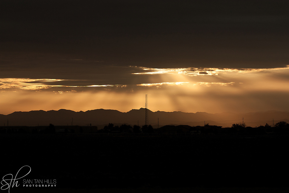 Beams of sunlight burst through cloud cover over San Tan Valley at sunrise