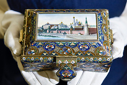 "© Licensed to London News Pictures. 22/11/2019. LONDON, UK. A technician presents ""A silver-gilt, cloisonné and pictorial enamel casket"", 1908-1917, by Feodor Ruckert, Moscow (Est. GBP100-150k) at the preview for the upcoming sales of Russian artworks at Sotheby's New Bond Street.  The Russian Pictures and Works of Art, Fabergé and Icons sales take place on 26 November.  Photo credit: Stephen Chung/LNP"