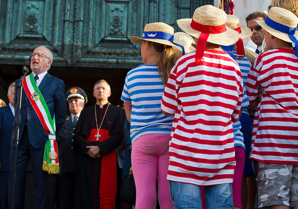 VENICE, ITALY - JULY 20:  Childrens wearing gondoliers shirts listen to the speaches of the Major of Venice and the Patriarch of Venice during the opening of the Redentore Celebrations on July 20, 2013 in Venice, Italy. Redentore is one of the most loved celebrations by Venetians which is in remembrance for the end of the 1577 plague. Highlights of the celebration include the pontoon bridge extending across the Giudecca Canal, gatherings on boats in the St Mark's basin and a spectacular fireworks display.  (Photo by Marco Secchi/Getty Images)
