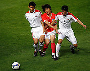 South Korea's Kim Do-heon (C) is challenged by North Korea's An Yong-hak (L) and Lee Kwang-chon during their 2010 World Cup qualifier soccer match at the Seoul World Cup stadium in Seoul June 22, 2008. Photo by Lee Jae-Won (SOUTH KOREA) www.leejaewonpix.com