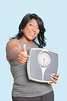 Portrait of woman giving thumbs up while holding scales over blue background