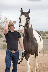 hot cowboy walking with a painted horse on a ranch