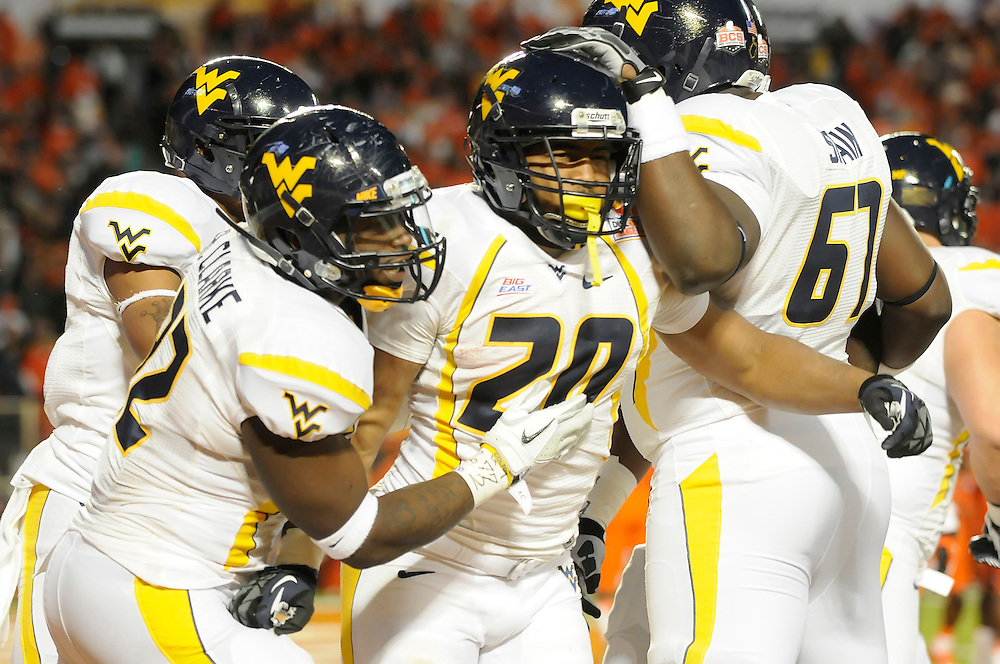 January 4, 2012: Shawne Alston of West Virginia is congratulated by Quinton Spain and Ryan Clarke after scoring a touchdown during the NCAA football game between the West Virginia Mountaineers and the Clemson Tigers at the 2012 Discover Orange Bowl at Sun Life Stadium in Miami Gardens, Florida.