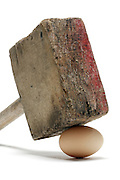 big wooden hammer balancing on top of an egg