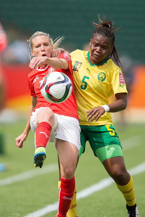 Switzerland's Lara Dickenmann (L) and Cameroon's Augustine Ejangue  vie for the ball during the first half of their FIFA Women's World Cup group C match at Commonwealth Stadium in Edmonton, Canada on June 16, 2015.   AFP PHOTO/GEOFF ROBINS