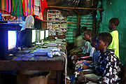 Young Malian teenagers play a football game on Sony Playstation game consoles at a market stall in the local market of Bamako, Mali.