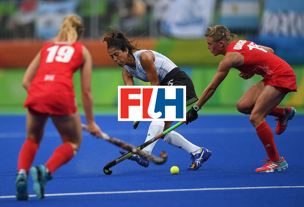 Argentina's Gabriela Aguirre tries to get past Britain's Sophie Bray and  Alex Danson during the women's field hockey Britain vs Argentina match of the Rio 2016 Olympics Games at the Olympic Hockey Centre in Rio de Janeiro on August, 10 2016. / AFP / MANAN VATSYAYANA        (Photo credit should read MANAN VATSYAYANA/AFP/Getty Images)