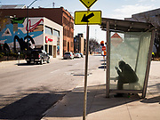08 APRIL 2020 - DES MOINES, IOWA: A man waits for a bus at a bus stop in downtown Des Moines. City streets are mostly empty and buses are running on a reduced schedule because most people are staying at home during the Coronavirus pandemic. On Wednesday, 08 April, Iowa reported 1,145 confirmed cases of the Novel Coronavirus (SARS-CoV-2) and COVID-19. There have been 27 deaths attributed to COVID-19 in Iowa. Most non-essential businesses are closed until 30 April.        PHOTO BY JACK KURTZ