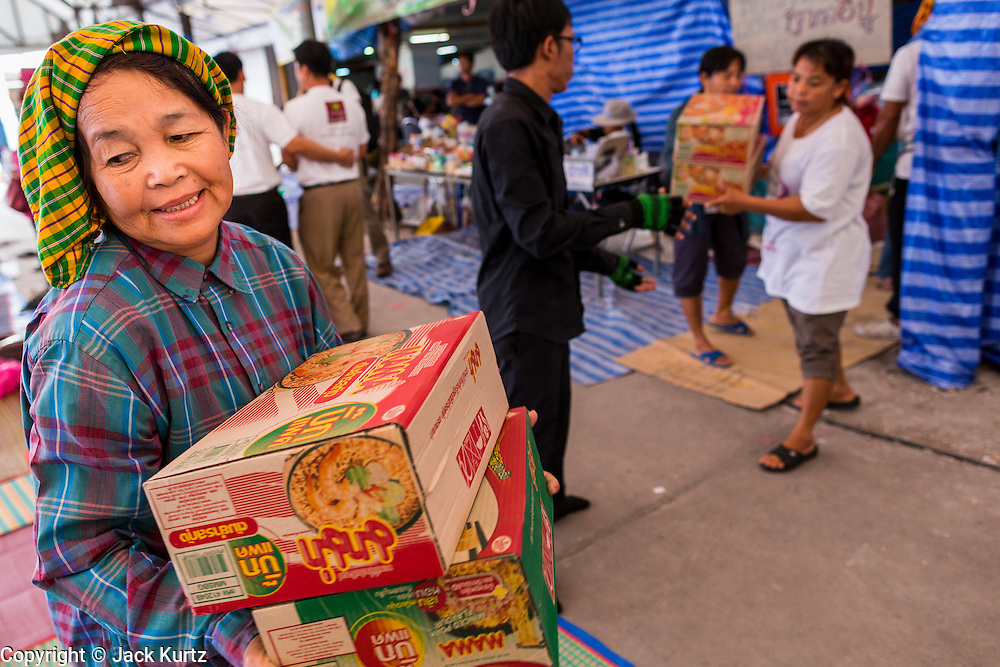 """13 FEBRUARY 2014  - NONTHABURI, NONTHABURI, THAILAND: Thai rice farmers pick up emergency rations donated to the farmers by members of the public at the Ministry of Commerce complex in Nonthaburi, outside of Bangkok. The Thai government instituted a """"rice pledging scheme"""" after the election in 2011. The government agreed to buy farmers' rice crops at above market prices then planned to warehouse the rice and sell it on international markets when prices recovered. At the same time, India and Vietnam started to export large quantities of rice and the Thai government fell short of funds to pay for rice it had already purchased from farmers. Many farmers have not been paid for rice grown in 2013 and some of the rice in the Thai warehouses is allegedly rotting. Thailand has fallen from number 1 rice exporter in the world to number 3 and several government to government contracts the Thais signed with rice importing countries (like China) have been cancelled. Farmers, once key supporters of the government are now joining anti-government protests in Bangkok and occupying government ministries including the Ministry of Commerce.    PHOTO BY JACK KURTZ"""